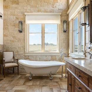 Foto di una stanza da bagno country con consolle stile comò, ante in legno bruno, vasca con piedi a zampa di leone, piastrelle marroni, pareti bianche, lavabo sottopiano, pavimento marrone e top beige