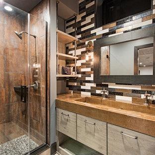 クリーブランドの中くらいのトランジショナルスタイルのおしゃれなバスルーム (浴槽なし) (フラットパネル扉のキャビネット、マルチカラーの壁、アルコーブ型シャワー、茶色いタイル、マルチカラーのタイル、横長型シンク、淡色木目調キャビネット、メタルタイル、淡色無垢フローリング、亜鉛の洗面台、茶色い床、開き戸のシャワー、ブラウンの洗面カウンター) の写真