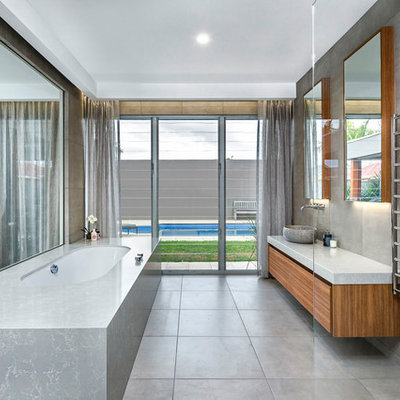 Trendy master gray tile and cement tile cement tile floor and gray floor bathroom photo in Adelaide with flat-panel cabinets, medium tone wood cabinets, an undermount tub, gray walls, a vessel sink and gray countertops