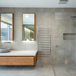 Bild på ett funkis beige beige en-suite badrum, med släta luckor, skåp i mellenmörkt trä, en hörndusch, beige kakel, cementkakel, beige väggar, cementgolv, ett fristående handfat, beiget golv och med dusch som är öppen