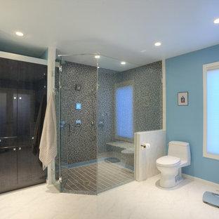Esempio di una stanza da bagno padronale design di medie dimensioni con lavabo sottopiano, ante lisce, ante marroni, top in superficie solida, doccia a filo pavimento, piastrelle multicolore, piastrelle di vetro, pareti blu e pavimento in gres porcellanato