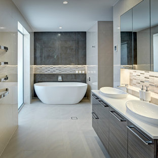 Inspiration for a large contemporary bathroom in Adelaide with a built-in sink, flat-panel cabinets, dark wood cabinets, solid surface worktops, a freestanding bath, beige tiles, porcelain tiles, beige walls and porcelain flooring.