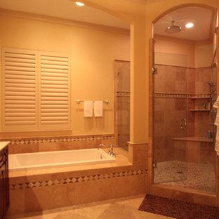 Immagine di una stanza da bagno padronale tradizionale con lavabo sottopiano, ante a filo, ante in legno bruno, vasca da incasso, doccia alcova, piastrelle beige, piastrelle di ciottoli, pareti beige e pavimento in travertino