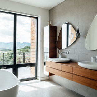 На фото: главные ванные комнаты в стиле модернизм с плоскими фасадами, фасадами цвета дерева среднего тона, отдельно стоящей ванной, серой плиткой, белыми стенами, настольной раковиной, столешницей из дерева, серым полом и коричневой столешницей