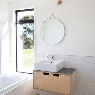 Inredning av ett nordiskt badrum med dusch, med släta luckor, skåp i ljust trä, ett platsbyggt badkar, vit kakel, vita väggar, plywoodgolv, ett fristående handfat och brunt golv