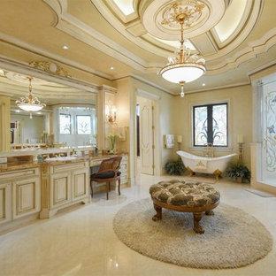 Idee per un'ampia stanza da bagno padronale mediterranea con ante con bugna sagomata, ante gialle, vasca con piedi a zampa di leone, doccia ad angolo, pareti gialle, pavimento in marmo, lavabo rettangolare, top in granito e porta doccia a battente