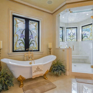 Bathroom - huge mediterranean master marble floor bathroom idea in Miami with raised-panel cabinets, yellow cabinets, yellow walls, a trough sink, granite countertops and a hinged shower door