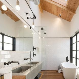 Стильный дизайн: ванная комната в стиле лофт с столешницей из дерева, белой плиткой, плиткой кабанчик, отдельно стоящей ванной, монолитной раковиной, белыми стенами, паркетным полом среднего тона, плоскими фасадами, фасадами цвета дерева среднего тона, открытым душем, открытым душем и коричневой столешницей - последний тренд