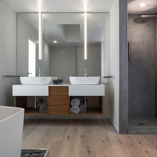 Свежая идея для дизайна: ванная комната в стиле модернизм с плоскими фасадами, фасадами цвета дерева среднего тона, отдельно стоящей ванной, угловым душем, серыми стенами, светлым паркетным полом, настольной раковиной, бежевым полом и белой столешницей - отличное фото интерьера
