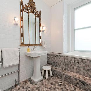 Ejemplo de cuarto de baño principal, bohemio, pequeño, sin sin inodoro, con bañera encastrada, sanitario de pared, baldosas y/o azulejos blancos, paredes blancas, suelo de baldosas de cerámica, lavabo con pedestal, encimera de madera, suelo gris y encimeras blancas
