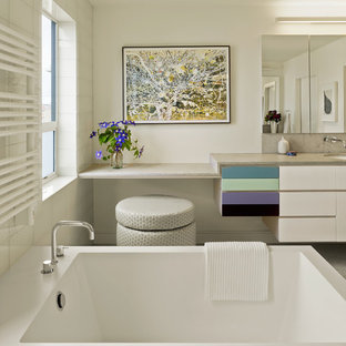 Example of a mid-sized trendy gray tile and mosaic tile mosaic tile floor freestanding bathtub design in San Francisco with an undermount sink, flat-panel cabinets, white cabinets, white walls, a one-piece toilet and granite countertops