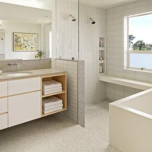 Immagine di una stanza da bagno padronale design con lavabo sottopiano, ante lisce, ante bianche, vasca freestanding, piastrelle bianche, pareti bianche, pavimento con piastrelle a mosaico, doccia a filo pavimento e top grigio