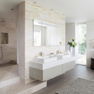 Photo of an expansive modern bathroom in London with flat-panel cabinets, grey cabinets, a walk-in shower, white walls, a wall-mounted sink, grey floors, an open shower and beige tiles.