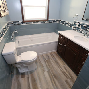 Photo of a mid-sized modern master bathroom in Orange County with raised-panel cabinets, dark wood cabinets, an alcove tub, an alcove shower, a one-piece toilet, blue tile, glass tile, blue walls, porcelain floors, an undermount sink, marble benchtops, blue floor, a hinged shower door, white benchtops, a shower seat, a single vanity and a built-in vanity.
