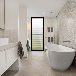 Design ideas for a beach style master bathroom in Sydney with flat-panel cabinets, white cabinets, a freestanding tub, beige tile, black and white tile, white walls, a vessel sink, beige floor and beige benchtops.