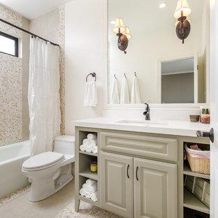Ispirazione per una piccola stanza da bagno chic con lavabo sottopiano, ante con bugna sagomata, ante beige, vasca ad alcova, vasca/doccia, WC monopezzo, piastrelle beige, piastrelle di ciottoli, pareti bianche, pavimento con piastrelle di ciottoli e top in quarzo composito