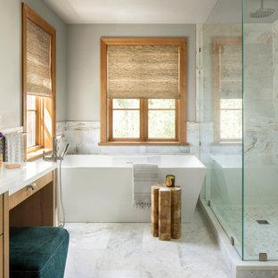 Cette image montre une grand salle de bain principale chalet avec un placard à porte plane, des portes de placard en bois brun, une baignoire indépendante, une douche d'angle, un WC à poser, un carrelage blanc, du carrelage en marbre, un mur gris, un sol en marbre, un lavabo encastré, un plan de toilette en quartz modifié, un sol blanc, une cabine de douche à porte battante, un plan de toilette blanc, un banc de douche, meuble double vasque, meuble-lavabo encastré et boiseries.