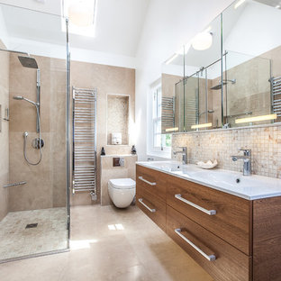 Inspiration for a contemporary shower room bathroom in London with flat-panel cabinets, dark wood cabinets, a corner shower, a wall mounted toilet, beige tiles, beige walls, an integrated sink, beige floors and white worktops.