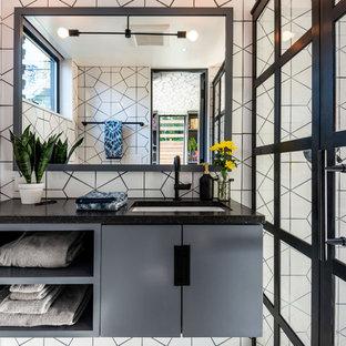 Immagine di una piccola stanza da bagno con doccia minimal con ante lisce, doccia alcova, piastrelle bianche, piastrelle in ceramica, lavabo sottopiano, top in superficie solida, porta doccia a battente, top nero e ante grigie