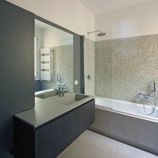 Ispirazione per una stanza da bagno padronale minimalista di medie dimensioni con lavabo da incasso, consolle stile comò, ante in legno bruno, top in cemento, vasca da incasso, WC sospeso, piastrelle grigie, piastrelle a mosaico, pareti grigie e pavimento in cemento