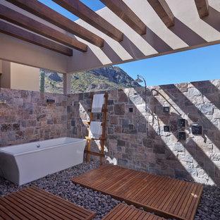 Foto de cuarto de baño de estilo americano, grande, con bañera exenta, ducha abierta, baldosas y/o azulejos grises, baldosas y/o azulejos de piedra, suelo marrón, ducha abierta, paredes grises y suelo de madera en tonos medios