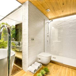 Foto di una stanza da bagno con doccia tropicale di medie dimensioni con doccia alcova, WC sospeso, pareti multicolore, pavimento in legno massello medio e lavabo a colonna