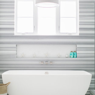 Inspiration for a medium sized coastal ensuite bathroom in Orange County with a freestanding bath, marble flooring, flat-panel cabinets, white cabinets, a corner shower, a one-piece toilet, white tiles, ceramic tiles, white walls, a submerged sink and engineered stone worktops.