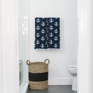 Maritim inredning av ett mellanstort badrum, med en hörndusch, en toalettstol med hel cisternkåpa, vit kakel, keramikplattor, vita väggar, ett undermonterad handfat, marmorbänkskiva, skiffergolv, luckor med profilerade fronter och blå skåp