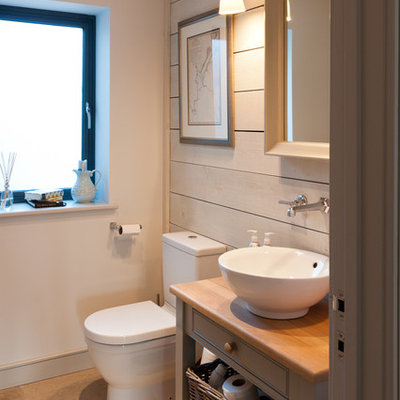 Small beach style ceramic tile and beige floor bathroom photo in Devon with a vessel sink, gray cabinets, white walls, shaker cabinets, a two-piece toilet, wood countertops and gray countertops