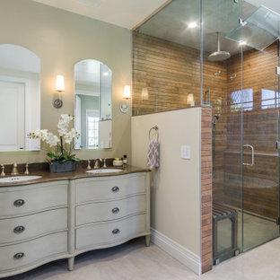 Inspiration för ett stort medelhavsstil brun brunt en-suite badrum, med möbel-liknande, beige skåp, ett fristående badkar, en kantlös dusch, porslinskakel, beige väggar, klinkergolv i porslin, beiget golv, dusch med gångjärnsdörr, ett undermonterad handfat, bänkskiva i akrylsten och brun kakel