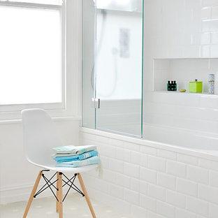 Ispirazione per una stanza da bagno per bambini design con vasca da incasso, vasca/doccia, piastrelle di cemento, pareti bianche e piastrelle bianche