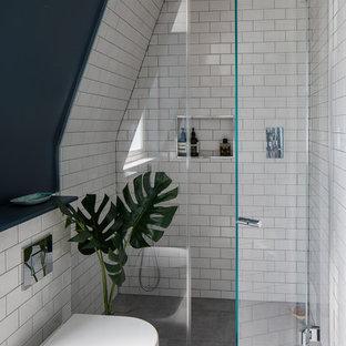 Modern inredning av ett litet en-suite badrum, med en öppen dusch, en vägghängd toalettstol, vit kakel, keramikplattor, cementgolv, grått golv, dusch med gångjärnsdörr och svarta väggar