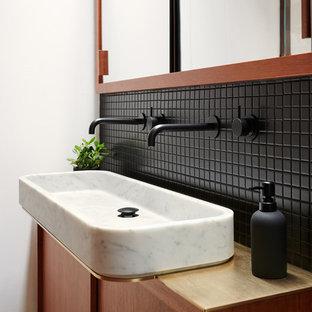 Ejemplo de cuarto de baño principal, contemporáneo, pequeño, con armarios con paneles lisos, puertas de armario de madera oscura, baldosas y/o azulejos negros, baldosas y/o azulejos de cerámica, paredes blancas, lavabo sobreencimera, encimera de madera y encimeras marrones