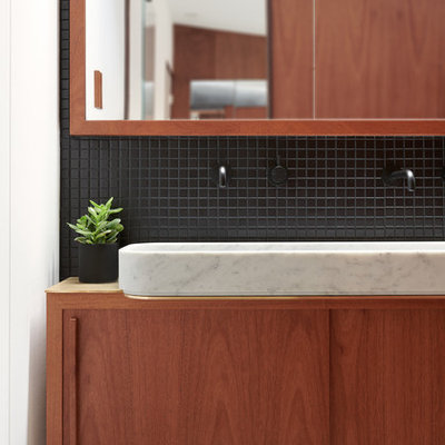 Small minimalist master black tile and ceramic tile concrete floor and gray floor bathroom photo in San Francisco with flat-panel cabinets, medium tone wood cabinets, a wall-mount toilet, black walls and a pedestal sink