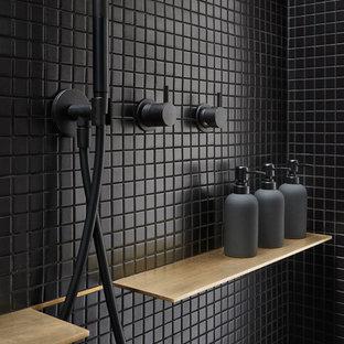Imagen de cuarto de baño principal, moderno, pequeño, con armarios con paneles lisos, puertas de armario de madera oscura, ducha doble, sanitario de pared, baldosas y/o azulejos negros, baldosas y/o azulejos de cerámica, paredes negras, suelo de cemento, lavabo con pedestal, suelo gris y ducha abierta