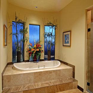 Idee per una stanza da bagno padronale tropicale di medie dimensioni con vasca da incasso, piastrelle beige, piastrelle in gres porcellanato, pareti gialle e pavimento in sughero