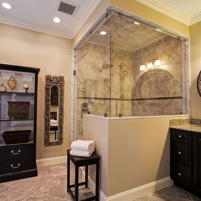 Inspiration for a mid-sized timeless master gray tile and porcelain tile porcelain tile corner shower remodel in Charlotte with an undermount sink, raised-panel cabinets, black cabinets, granite countertops and beige walls