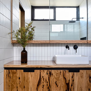 Example of a mid-sized trendy master white tile and subway tile terrazzo floor and gray floor bathroom design in Other with furniture-like cabinets, light wood cabinets, white walls, a vessel sink, wood countertops and a hinged shower door