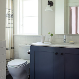 Photo of a medium sized classic family bathroom in Seattle with shaker cabinets, blue cabinets, an alcove bath, a two-piece toilet, ceramic tiles, white walls, lino flooring, a submerged sink, engineered stone worktops, black floors, a shower curtain, white worktops and white tiles.