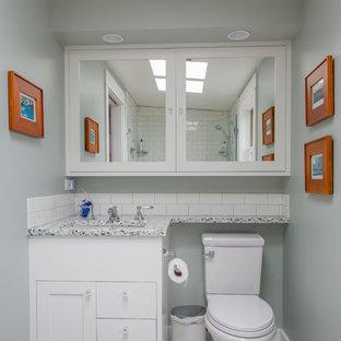 Foto på ett amerikanskt badrum, med släta luckor, vita skåp, en dusch i en alkov, en toalettstol med hel cisternkåpa, vit kakel, tunnelbanekakel, vita väggar, klinkergolv i keramik, ett undermonterad handfat och bänkskiva i återvunnet glas