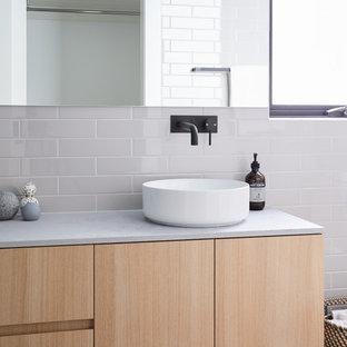 Ejemplo de cuarto de baño nórdico, pequeño, con puertas de armario de madera clara, bañera exenta, ducha abierta, baldosas y/o azulejos grises, baldosas y/o azulejos de cemento, paredes grises, suelo de terrazo, encimera de cemento, suelo gris, ducha abierta y encimeras grises