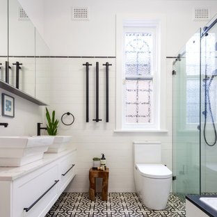 Mid-sized contemporary bathroom in Sydney with shaker cabinets, white cabinets, a corner tub, a corner shower, a one-piece toilet, white tile, porcelain tile, white walls, porcelain floors, black floor, a sliding shower screen, grey benchtops, a niche, a double vanity and a built-in vanity.