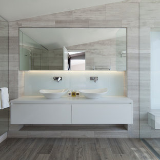 Foto di una grande stanza da bagno padronale moderna con doccia aperta, ante lisce, ante bianche, piastrelle grigie, piastrelle in travertino, pavimento in travertino, lavabo a bacinella, top in quarzite, pavimento grigio e doccia aperta