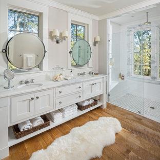 Foto de cuarto de baño principal, rústico, con armarios con rebordes decorativos, puertas de armario blancas, ducha a ras de suelo, baldosas y/o azulejos blancos, paredes beige, suelo de madera en tonos medios, lavabo bajoencimera y encimeras blancas