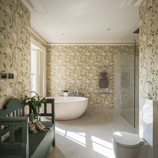 Photo of a traditional ensuite bathroom in Surrey with a freestanding bath, a two-piece toilet, beige walls and grey floors.