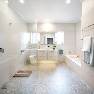 メルボルンの中サイズのモダンスタイルのおしゃれなバスルーム (浴槽なし) (フラットパネル扉のキャビネット、ベージュのキャビネット、ドロップイン型浴槽、段差なし、一体型トイレ、ベージュのタイル、磁器タイル、ベージュの壁、テラゾの床、オーバーカウンターシンク、珪岩の洗面台、マルチカラーの床、オープンシャワー、白い洗面カウンター) の写真