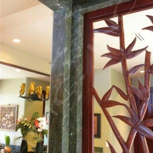 Immagine di una grande stanza da bagno tropicale con ante in legno bruno, vasca sottopiano, piastrelle verdi, lastra di pietra, lavabo a bacinella, top in granito e top verde