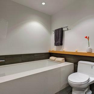 Idee per una stanza da bagno con doccia moderna di medie dimensioni con vasca sottopiano, WC monopezzo, piastrelle grigie, pareti bianche e pavimento in gres porcellanato