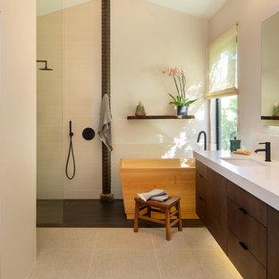 Идея дизайна: большая главная ванная комната в восточном стиле с плоскими фасадами, фасадами цвета дерева среднего тона, японской ванной, душем без бортиков, раздельным унитазом, белой плиткой, полом из керамогранита, врезной раковиной, столешницей из искусственного камня, бежевым полом, душем с раздвижными дверями, белой столешницей, белыми стенами, тумбой под две раковины, встроенной тумбой и сводчатым потолком
