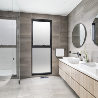 Contemporary bathroom in Melbourne with flat-panel cabinets, light wood cabinets, gray tile, a vessel sink, grey floor, white benchtops and a double vanity.